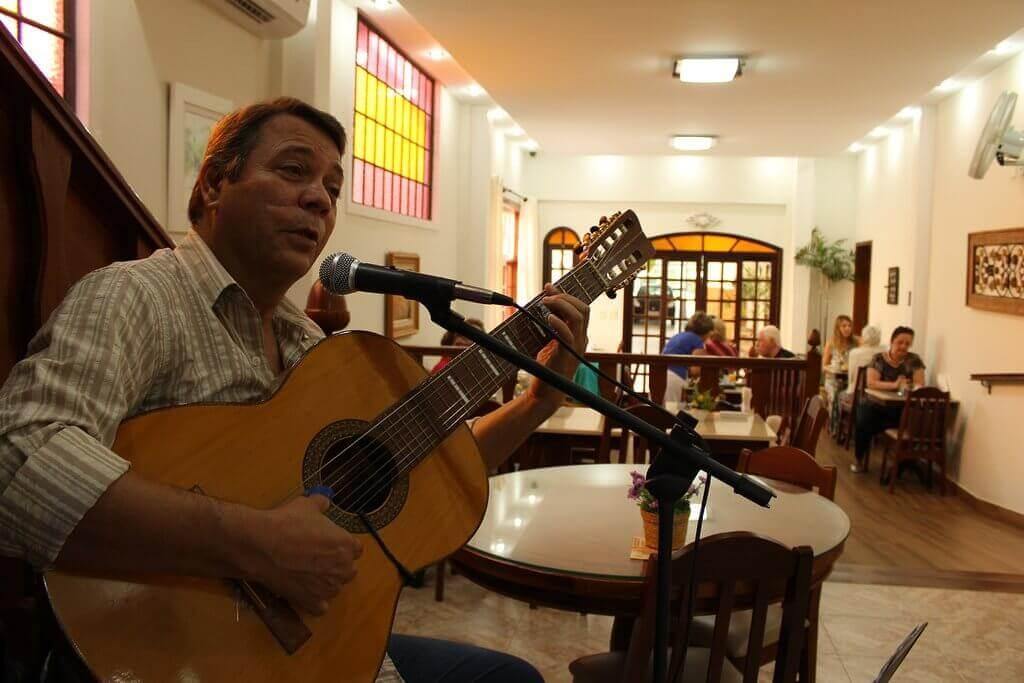 foto de um violeiro cantantando e tocando no café da manhã da Pousada Luar da Serra